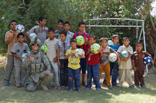 Pfc. Dominick Skompski (bottom left), an armor crewman with Company D, 3rd Battalion, 69th Armor Regiment, 1st Advise and Assist Brigade, 3rd Infantry Division, United States Division - Center, poses with Iraqi children Sept. 13 after distributing soccer balls to them in Baghdad. The soccer balls were donated by Americans through the Winning Hearts and Minds Project, created by Skompski's father, Joe D'Alessandro, president of the Cohansey Soccer Club in Upper Deerfield Township, N.J.