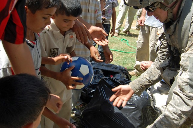 Pfc. Dominick Skompski (right), an armor crewman with Company D, 3rd Battalion, 69th Armor Regiment, 1st Advise and Assist Brigade, 3rd Infantry Division, United States Division - Center, passes out soccer balls to Iraqi children Sept. 13 in a rural area of Baghdad. The soccer balls were donated by Americans through the Winning Hearts and Minds Project, a charity created by Skompski's father, Joe D'Alessandro, president of the Cohansey Soccer Club in Upper Deerfield Township, N.J.