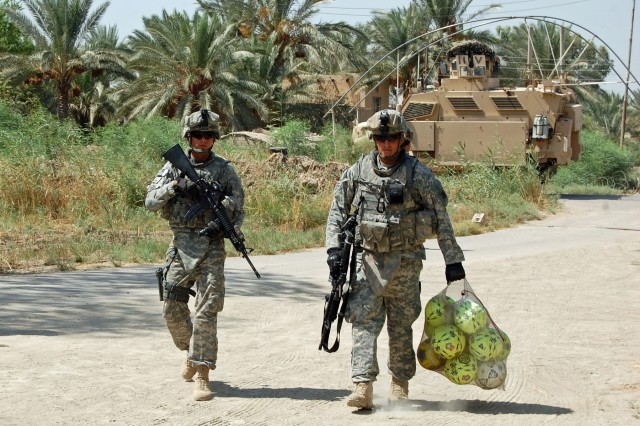Cpl. Jonathan Holloway (left), with Company D, 3rd Battalion, 69th Armor Regiment, 1st Advise and Assist Brigade, 3rd Infantry Division, United States Division - Center, provides security Sept. 13 for Spc. Neil Weaver, also with Co. B, while he carries a bag of soccer balls to be distributed to Iraqi children in a rural area of Baghdad.