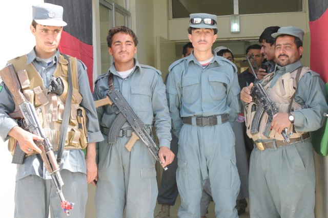 """Afghan National Police officers stands guard at the door of the ANP station awaiting the start of a ribbon cutting ceremony signifying the opening of the province's new substation in Spin Boldak Sept. 21.  """""""