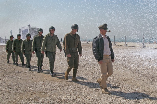 Gen. Douglas MacArthur, depicted by Marine Capt. Michael Borneo, right, marches across the beach amid a flurry of confetti, with fellow Marines depicting his key officers in tow during reenactment ceremonies of the Inchon Landing in the Republic of Korea, Sept. 15, 2010.