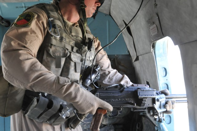 KANDAHAR AIRFIELD, Afghanistan - U.S. Air Force Tech. Sgt. Frank Dirr, a Victoria, Texas, native, is a crew chief with the 442nd Air Expeditionary Advisory Squadron and conducts pre-flight checks on the AKM (7.62mm assault rifle) on board the MI-17 helicopter Sept. 22. Afghan and American pilots flew two MI-17 helicopters on a routine troop movement mission to several forward operating bases throughout the southern part of Afghanistan in support of Operation Enduring Freedom.