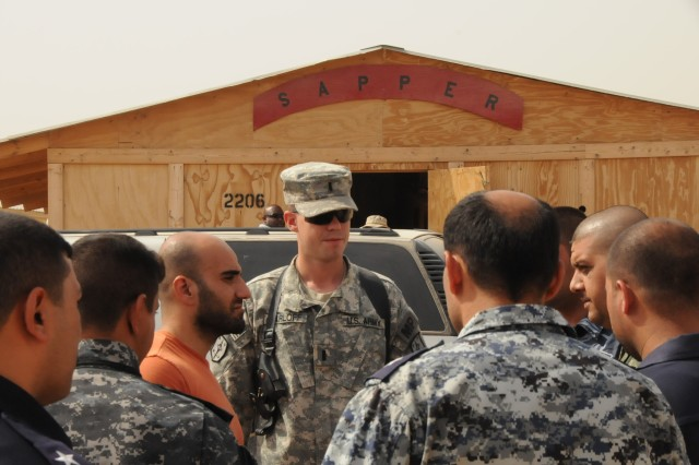 First Lieutenant Steven Harloff, a platoon leader with the 512th MP Co., listens to Iraqi police officers going over their plan during crime scene investigation training Sept. 21 at Forward Operating Base Warhorse. The MP Soldiers monitored the training and offered invaluable assistance to improve on the IPs crime fighting skills.