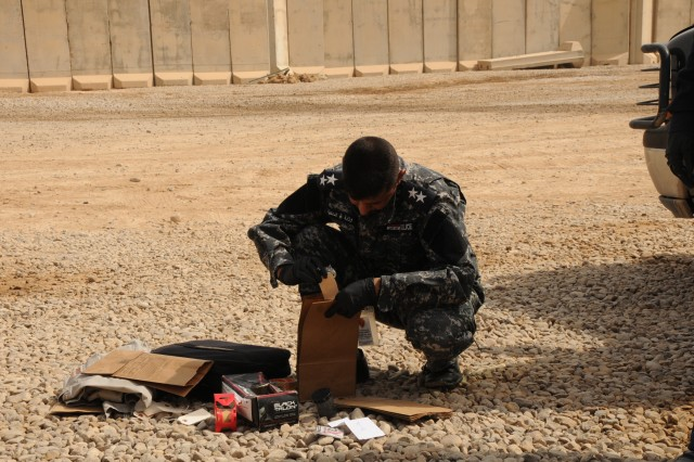 An Iraqi police officer goes over evidence found during crime scene investigation training Sept. 21 at Forward Operating Base Warhorse.