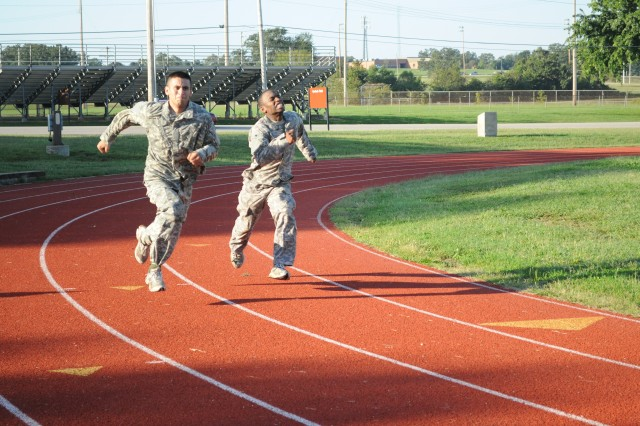 Spc. Juan Trevino  and Spc. Willie Shepard, both 988th Military Police Company, sprint toward the finish line during the Special Forces Qualification Physical Fitness Test, Sept. 23., on Gerlach Field. The test is the standard APFT, but must be conducted in Army Combat Uniform.