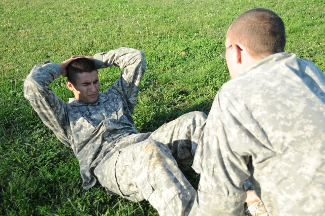 Spc. Juan Trevino performs a sit up as Pvt. Alexander Maggiore, both 988th Military Police Company, Fort Leonard Wood, Mo., holds his feet during the Army Physical Fitness Test for acceptance into Special Forces training, Sept. 23.