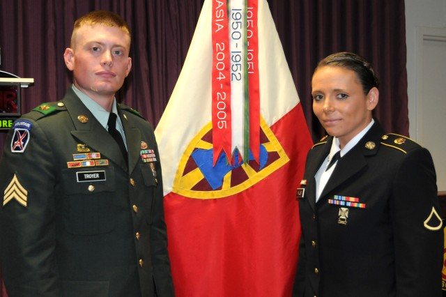 Winners: Sergeant Daniel Troyer, (left), a 611th Seaport Operations Company, 6th Transportation Battalion squad leader and Private 1st Class Frieda Miller, a 7th Sus. Bde. Paralegal, stand with the brigade colors after winning the Noncommissioned Officer and Soldier of the Year competition Sept. 28. (U.S. Army photo Spc. Krista Howell)