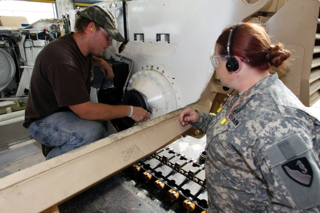 Sgt. Angel Herrera stops to talk to Anniston Army Depot mechanic Kenneth Langley during her tour of the installation's combat vehicle production operations.