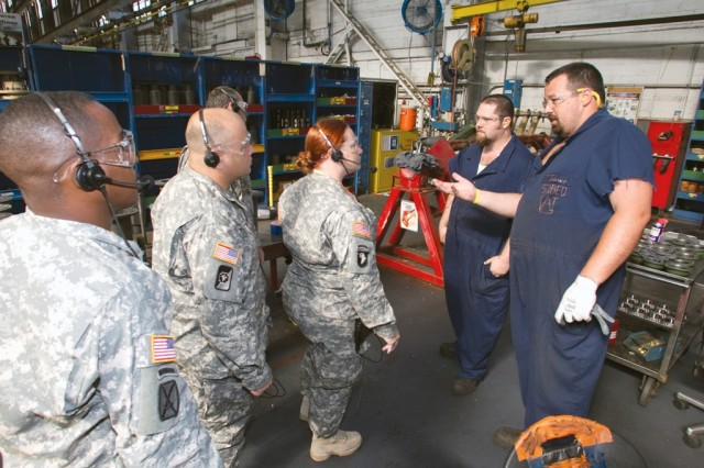 Anniston Army Depot mechanics Jason Joiner, right, and Chad Phillips greet Soldiers from Fort Hood's Warrior Transition Brigade Sept. 14 in the depot's Combat Vehicle Repair Facility.
