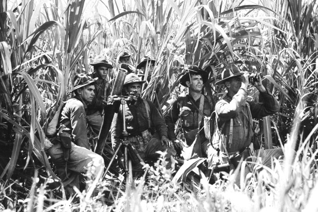 Soldiers of the 65th Infantry take cover in a sugar cane field near Salinas, Puerto Rico, November 1941.