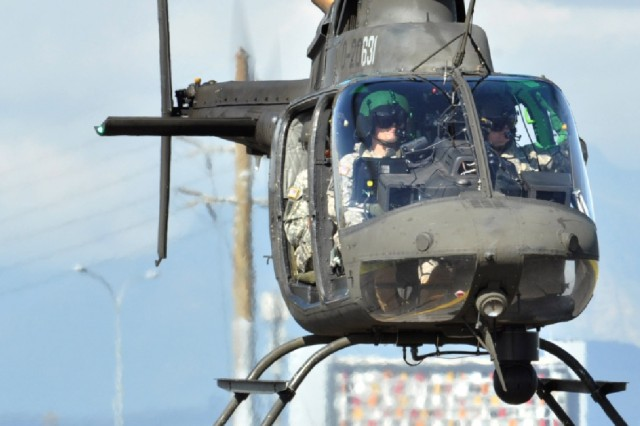 Brig. Gen. Renwick Payne, New York National Guard director of joint staff, and Chief Warrant Officer 3 Aaron Teichner, (front left) an aviator with Det. 1 A Co 1-224 Aviation Security and Support Battalion, fly in an OH-58 Kiowa Sept 22, at Air Force Base Ysterplaat, Cape Town, South Africa.  The U.S Army is participating with other military forces throughout the world during the Africa Aerospace & Defence (AAD) 2010 exhibition.  The event is Africa's premier aerospace, general aviation, defense and security expo that includes a world class air show, dynamic vehicle demonstrations and many other static displays.