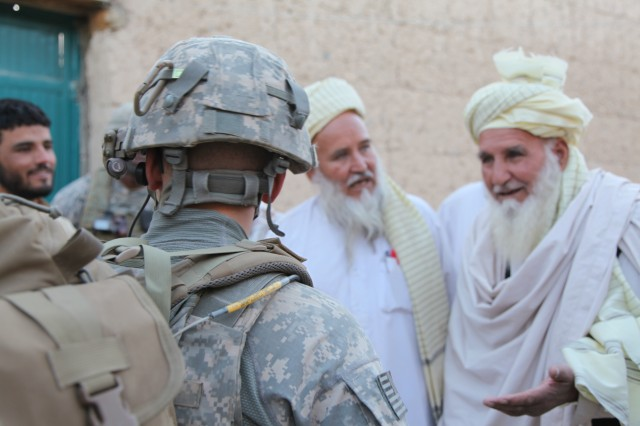 A Paratrooper from 503rd Infantry Regiment, 173rd Airborne Brigade Combat Team speaks with village elders in Chak District, Wardak province, during Operation Talon Purge, Sept. 24.