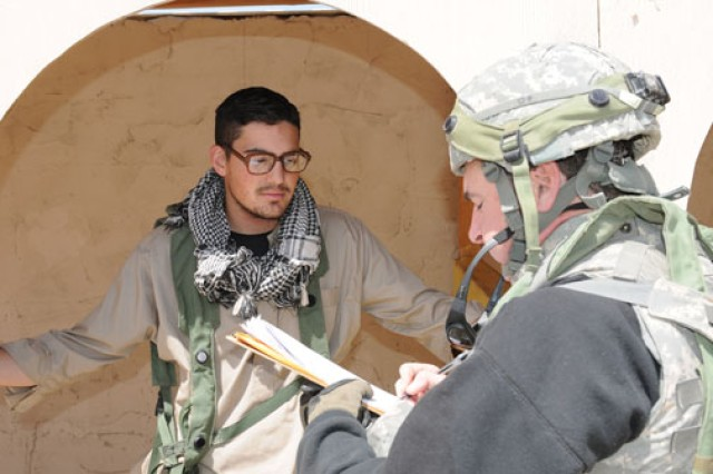 """Dr. James Forsythe, a social scientist with an Army Human Terrain Team, interviews an """"Iraqi civilian"""" in the simulated village of Abar Layla, at the U.S. Army National Training Center at Fort Irwin, Calif."""