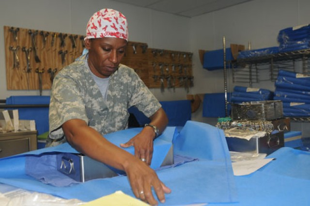 Staff Sgt. Judi Reeves, a surgical technician at Forward Operating Base Salerno, folds cloth over a vascular surgical tray of medical instruments before placing it into a sterilizing machine.