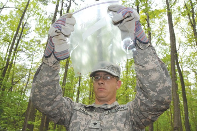 Spc. John Hall studies a mock bone fragment after it was unearthed at a clandestine gravesite during the seminar.