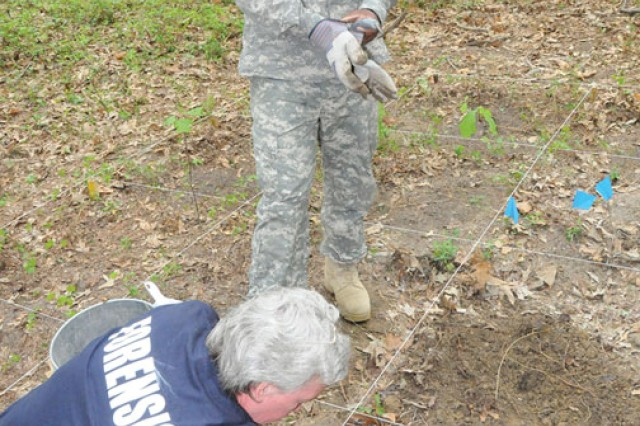 Dr. Lisa Leppo, chief of training, Joint Mortuary Affairs Center, demonstrates to Spc. Earl Harden how to proceed when remains are found in a clandestine burial.