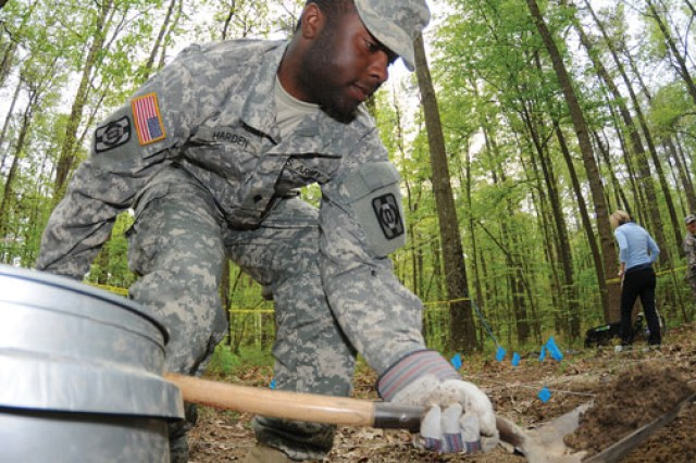 Spc. Earl Harden gently shovels dirt from a site thought to hold remains during the Unidentified Human Remains Seminar, which took place at Fort Lee, Va., in April. The exercise-also depicted on the opposite page-was designed to familiarize mortuary affairs personnel with procedures used in finding buried human remains.
