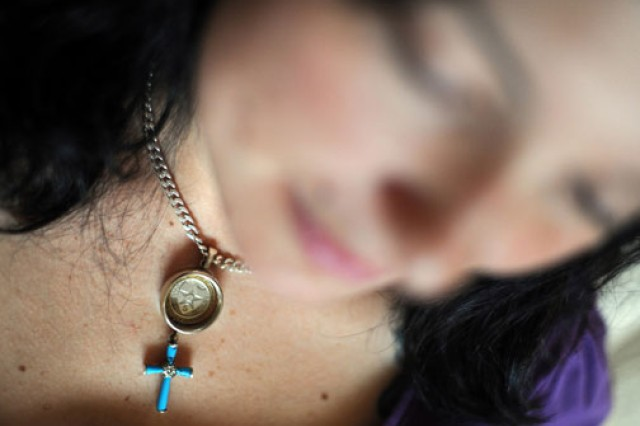 Erica Paci wears a necklace made of her husband's wedding ring, the 5th Brigade, 2nd Infantry Division coin and a cross that he purchased in Afghanistan and gave her at Christmas, just months before his death.
