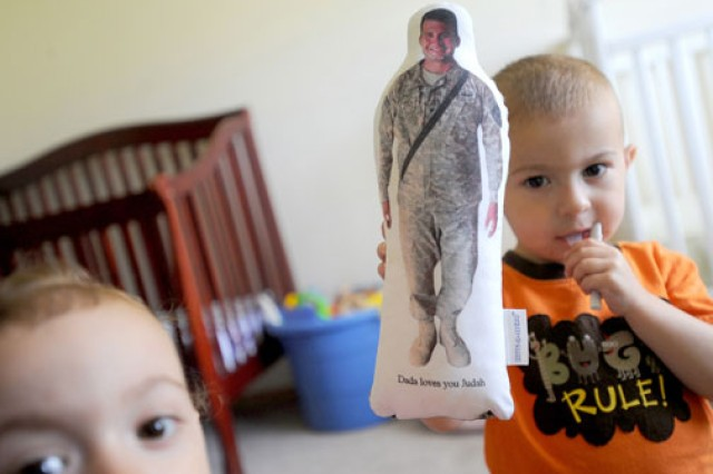 """Judah Paci, right, holds his """"Daddy doll"""" as his sister, Tallulah, plays in their new Steilacoom, Wash., home. Their mother, Erica, is keeping their late father's memory alive for them."""