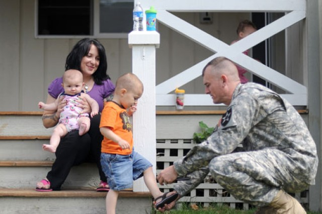 "Sgt. 1st Class Jonathan Otis, a casualty assistance officer, helps Judah Paci put on his sandal as his mother, Erica, looks on at her Steilacoom, Wash., home. Erica's husband, Sgt. Anthony ""Tony"" Paci, was killed in Afghanistan in March."