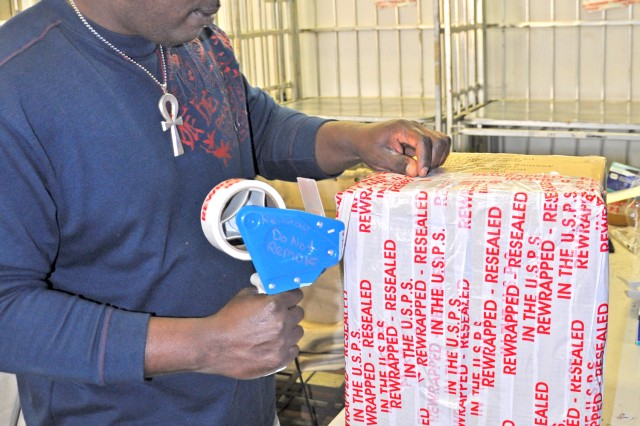 Quintin Harvey, Wiesbaden postal operations supervisor, tapes a damaged parcel upon arrival at the Wiesbaden Postal Service Center.
