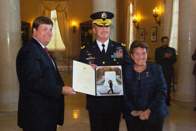 Maj. Gen. Karl Horst, commander of the Joint Force Headquarters National Capital Region and the U.S. Army Military District of Washington, presents a certificate commemorating a wreath laying at the Tomb of the Unknowns to Joan Argenzio, the widow of the youngest infantryman on Omaha Beach during World War Two, and Pete Humes, chairman of the board with the Fredericksburg Virginia's Chamber of Commerce Military Affairs Council.