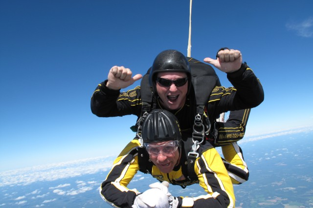 Director of Academics in Motion Jim Presbrey smiles for the camera during the freefall part of his tandem jump with Army Golden Knights Staff Sgt. Joseph Jones Sept. 28. 