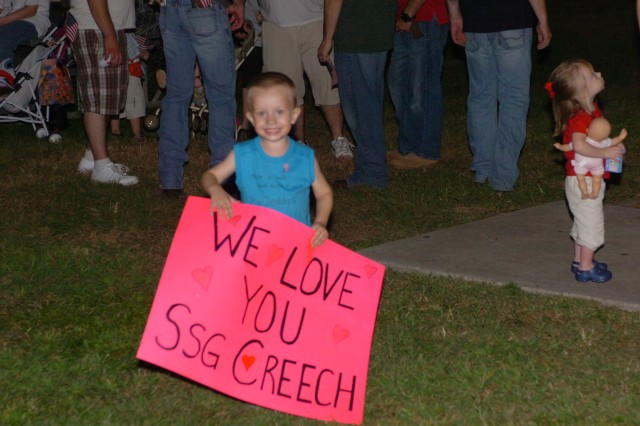 William Creech III holds up a sign welcoming home his father, Staff Sgt. William Creech, who returned home from Afghanistan with the 526th Engineer Company, at Cottrell Field on Fort Stewart, Sept. 24.