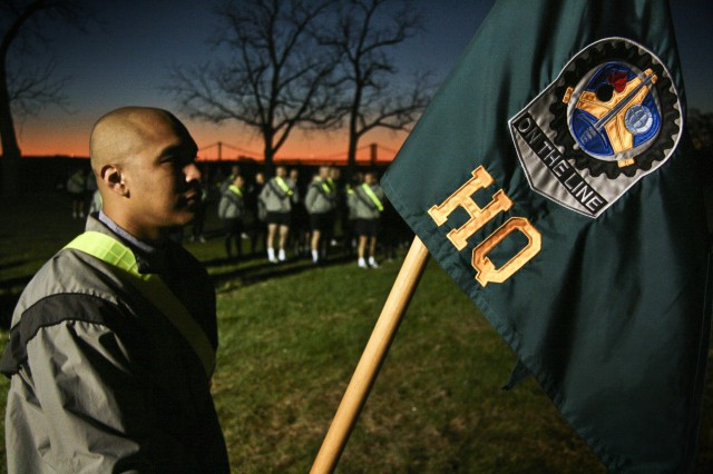 """Army Spc. Luis Ochoa holds the Headquarters Company guidon during an early morning formation at the Rock Island Arsenal, Ill., sports complex, Oct. 1. Arsenal servicemembers, along with their civilian counterparts, took time to reinforce the """"one team"""" mentality and play a few games. (Photo by Sgt. 1st Class Sean Riley, ASC Public Affairs)"""