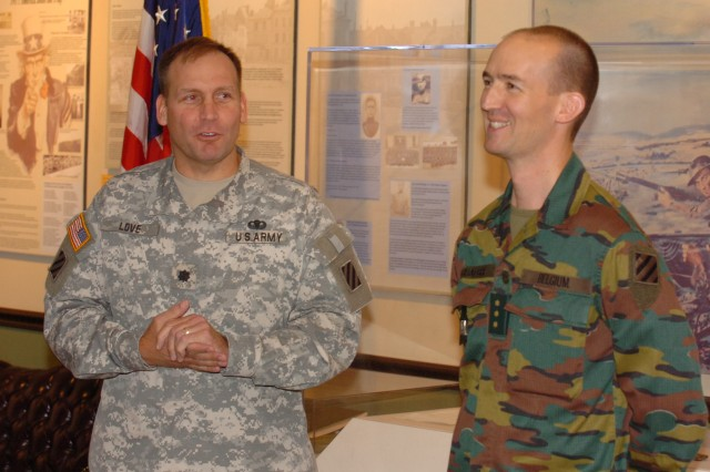Belgian Army Major Jeroen Verhaeghe (right), listens at Lt. Col. Christopher Love, rear deatchment commander for 3rd Infantry Division, speak at his promotion ceremony held at Fort Stewart's marne Museum. Major Verhaeghe came to work for the division as part of MPEP.