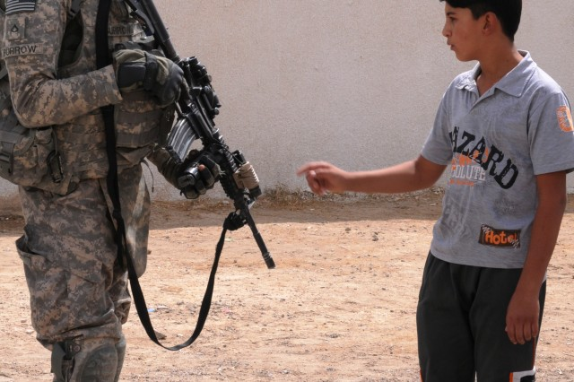 Private First Class Tyrice Burrow, a Soldier with A Co., 1st Battalion, 27th Infantry Regiment, 2nd Advise and Assist Brigade, 25th Infantry Division, captures the attention of a local Iraqi boy fascinated with his weapon while pulling perimeter security outside the Al Samad grade school in Al Alam, Salah ad Din province, Iraq. The school was part of a contract inherited by 2nd AAB, 25th ID.