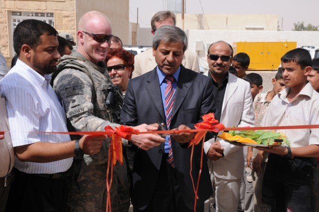 Lieutenant Colonel Donald Brown, the battalion commander for 1st Battalion, 27th Infantry Regiment, 2nd Advise and Assist Brigade, 25th Infantry Division, and Arif Mutter from the Tikrit City Council, prepare to cut a ribbon signifying the official opening of the Al Samad grade school in Al Alam, Salah ad Din province, Iraq. The school was part of a contract inherited by 2AAB, 25th ID.