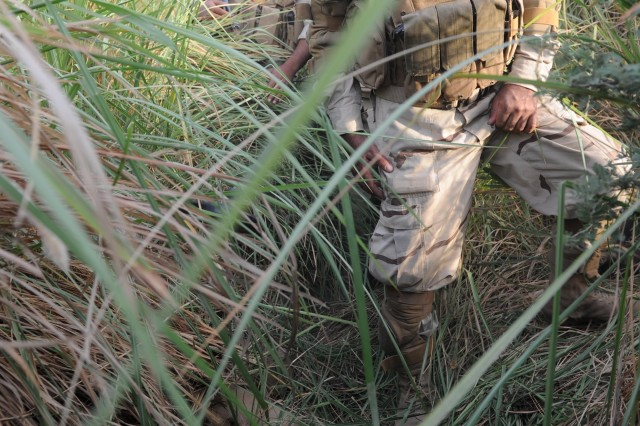 An Iraqi Army search for weapons during a cordon and search, in the Rashaad Valley near Kirkuk, Iraq, Sept. 25.  The Iraqi Army led operation ended with the soldiers discovering a cache with more than 800 rounds of heavy machine gun ammo and detaining four suspects.