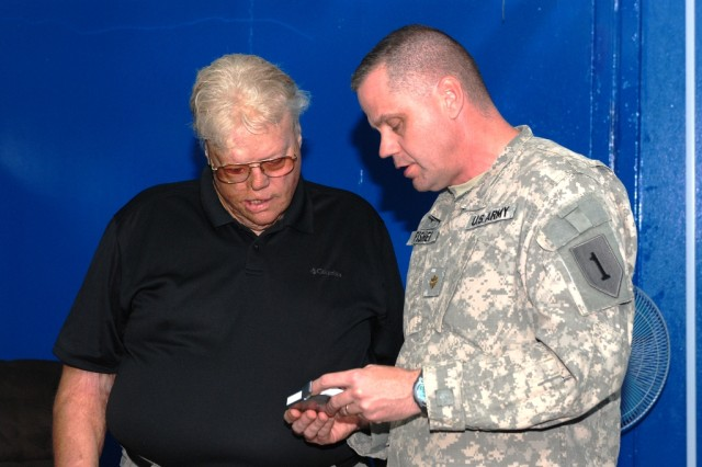 Maj. Gary Fisher, right, the deputy chaplain for United States Division-South, demonstrates a bio-feedback device to Dave Roever at the USD-S Resiliency Campus Sept. 29. The resiliency campus is a place where servicemembers can strengthen the Five Pillars of Comprehensive Soldier Fitness: physical, emotional, social, spiritual and Family.