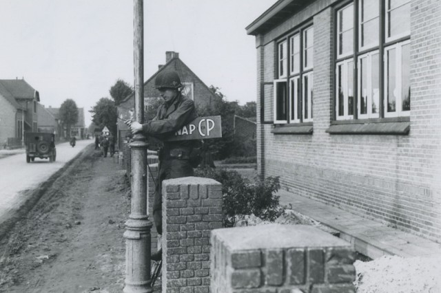 """A Soldier from the U. S. Army's 506th Parachute Infantry Regiment, 101st Airborne Division, hangs a command post sign with the regimental callsign, """"Kidnap,"""" during the Allied liberation of Holland in October 1944.  (George Koskimaki"""
