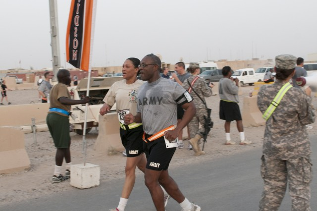 (Center) Sergeant Major Charles Friend, the senior signal noncommissioned officer for Task Force Marne, crosses the finish line in the Top of Iraq 10 km run held at Contingency Operating Base Speicher, Iraq, Sept. 24. The Top of Iraq run was the second of a series of three runs ending with the TF Marne 10-Miler which will be held Oct. 10.