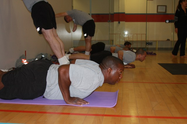 "Staff Sgt. Carlos Pride holds a low plank position during the Wednesday morning yoga class for 1st Platoon, Charlie Company, Warrior Transition Batallion-Europe. Certified yoga instructor Erika Liem Palidar, standing at right, customizes the weekly PT session to meet the specific physical needs of WTU Soldiers. Far from new-age relaxation, the hour-long class increases flexibility, strengthens core muscles and in the words of Palidar, ""unites body, mind and spirit."""