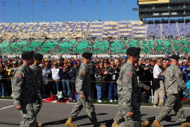Soldiers of the 4th Infantry Brigade Combat Team, 1st Inf. Div. receive cheers as they march past spectators Oct. 3 at the Kansas Speedway.