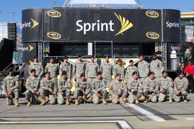 Soldiers of the 4th Infantry Brigade Combat Team, 1st Inf. Div. pose for a picture before they assist with the opening ceremonies of the Price Chopper 400, Oct. 3 at the Kansas Speedway. After the drivers' names were anounced they walked past and shook hands with the Soldiers before returning to their cars to start the race.