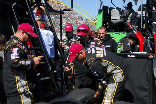 Members of the number 39 U.S. Army racing team wear hats representing the 'Big Red One,' Oct. 3 during the Price Chopper 400 race at the Kansas Speedway.