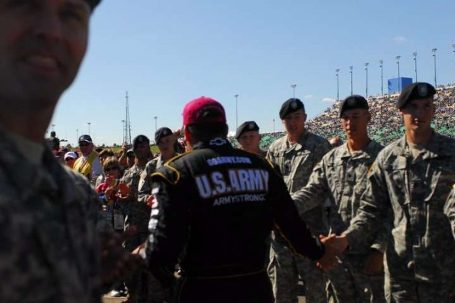 Soldiers of the 4th IBCT, 1st Inf. Div. shake hands with Ryan Newman, driver of the number 39 U.S. Army race car, Oct. 3, prior to the start of the Price Chopper 400 race at the Kansas Speedway.