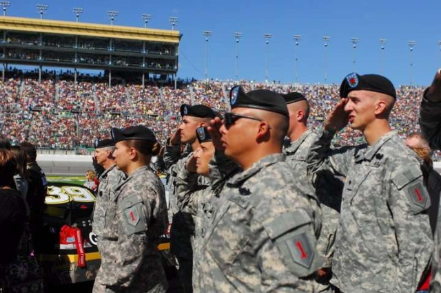 Soldiers of the 4th IBCT, 1st Inf. Div. salute from the in field, Oct. 3 during the playing of the National Anthem prior to the start of the Price Chopper 400 race at the Kansas Speedway.