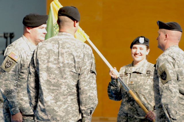 Maj. Beth Richardson, the incoming commander of the U.S. Army Regional Correctional Facility-Europe, takes hold of the new guidon to signify the change of command from Maj. Chad Goyette, the former facility commander, for the newly named confinement facility during a ceremony Sept. 29 at the Coleman Gym in Mannheim, Germany.