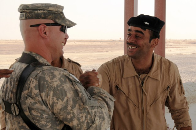 """Staff Sgt. Randy Christenson, the outgoing M1A1 tank combat advisor -- known by the call sign """"Black Seven"""" -- who is a member of Iraq Training and Advisory Mission-Army at the Besmaya Combat Training Center, congratulates an Iraqi Army M1A1 Tank Familiarization Course cadre on a successful training exercise Sept. 24. Christenson, a native of Dupont, Wash., said he's built relationships with the Iraqis cadre; respects the work they're doing and is going to miss them. """"I never say goodbye; I always say see you later,"""" he said. """"Even though I'll probably never see them again, they are difficult to walk away from. There's some emotion there."""""""