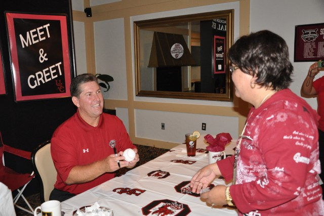 Ray Tanner, head coach of the University of South Carolina baseball team, autographs a baseball for Elvira Pading Tuesday during the Food Expo at the NCO Club. The USC baseball team won this year's College World Series.