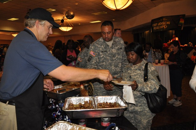 Tim Butler, Cherokee Foods Inc., serves lean sausage and baked chicken to Master Sgt. Claudia Polite and Sgt. 1st Class Michael Walker, both with the 175th Maintenance Company, during Tuesday's Food Expo. This year's expo showcased the dining facilities' healthful food options.