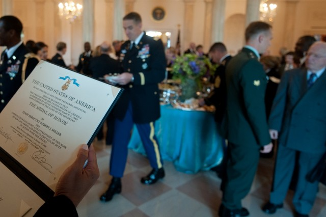 An Army member reads the Medal of Honor citation for Staff Sgt. Robert J. Miller following a ceremony in the East Room of the White House in Washington, D.C., Oct. 6, 2010.  Miller was posthumously awarded the honor for his heroic actions in Afghanistan, displaying immeasurable courage and uncommon valor eventually sacrificing his own life to save the lives of his teammates and 15 Afghanistan National Army soldiers.