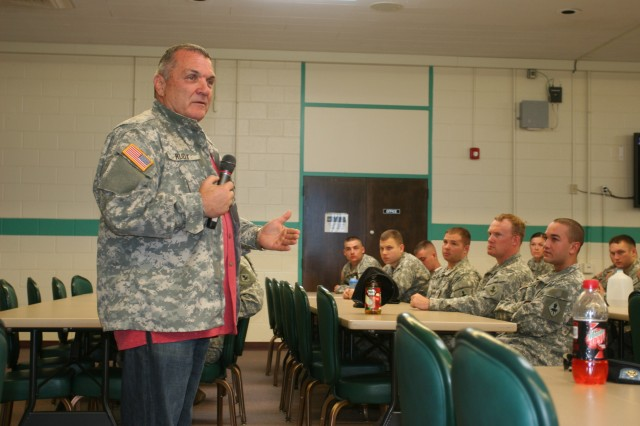 """Daniel Eugene """"Rudy"""" Ruettiger (left) speaks to Soldiers from the 18th Military Police detachment, during a professional development session at Murr Community Center. Prior to the session, the Soldiers presented Ruettiger with an Army combat uniform jacket, adorned with his name."""