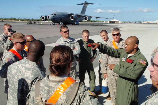 HICKAM AIR FORCE BASE, Hawaii- U.S. Air Force Tech Sgt. Isaiah Murray, 535th Airlift Squadron, briefs members of the U.S. Army, Pacific Contingency Command Post Deployable Assessment Team prior to loading equipment onto a C-17 cargo aircraft (in background) at Hickam Air Force Base, Hawaii.
