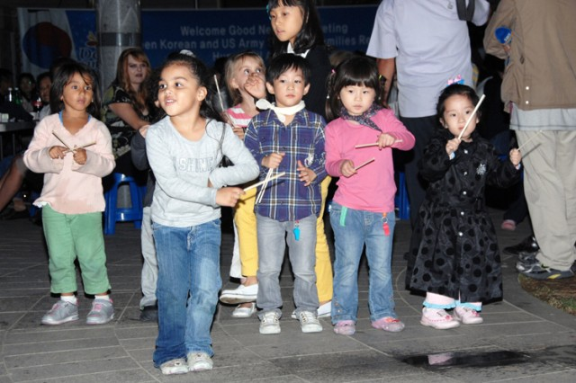 """Korean and American children living in the Human Vill Apartment show they know how to get along with their neighbors as they sway to the beat of a four-piece Dongducheon City Pungmul band, """"Edam,"""" during the Good Neighbor Meeting Sept. 27."""